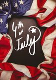 White fourth of July party graphic against chalkboard and american flag. Digital composite of White fourth of July party graphic against chalkboard and american Royalty Free Stock Image