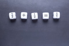 White fraction mah number dices showing simple equation on black Stock Images
