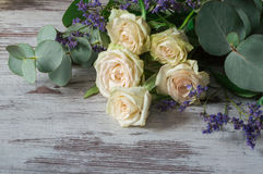 White fragrant roses with branches of eucalyptus on gray background. White fragrant roses with some branches of eucalyptus on gray background Stock Photo