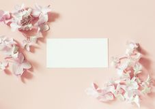 Styled feminine flat lay on pale pastel pink background, top view. Minimal woman`s desktop with blank page mock up, open envelope. White frame blank, pink stock image