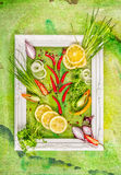White frame with chives, spices and lemon slice , composing on green  background Stock Images