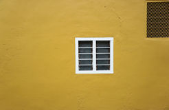 White frame glass louvers on the bright yellow wall Stock Photos