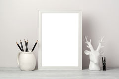 White frame mock up with pencil and decor deer. Modern stylish interior background for social media. And marketing Stock Image
