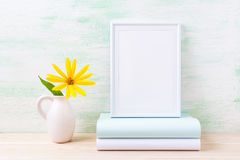 White frame mockup with bright yellow flowers and books Stock Photos