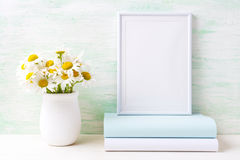 White frame mockup with chamomile bouquet in rustic vase and boo Royalty Free Stock Photography