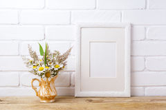 White frame mockup with chamomile and grass in golden vase stock photography