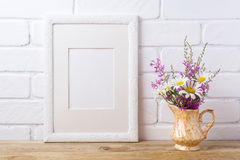 White frame mockup with chamomile and purple flowers in golden p Stock Images