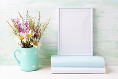 White frame mockup with chamomile and purple flowers in mint green pitcher and books. White frame mockup with white chamomile and purple field flowers in mint stock photos