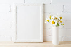 White frame mockup with daisy flower near painted brick wall. White frame mockup with daisy flower in styled vase near painted brick wall. Empty frame mock up stock images