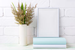 White frame mockup with  grass and green leaves in cylinder vase Stock Photo