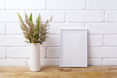 White frame mockup with  grass and green leaves in cylinder vase Royalty Free Stock Image