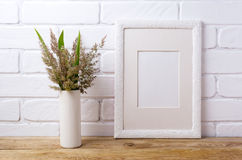 White frame mockup with grass and green leaves in cylinder vase Royalty Free Stock Photos