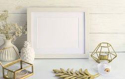 White frame mockup with interior items. On light wooden background. Copy space royalty free stock image