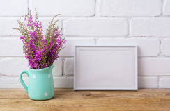 White frame mockup with maroon purple flowers in mint pitcher Royalty Free Stock Photography