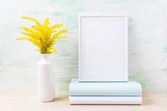 White frame mockup with ornamental golden grass and books Royalty Free Stock Image