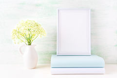 White frame mockup with pale mint book. Empty frame mock up for presentation artwork Royalty Free Stock Photo