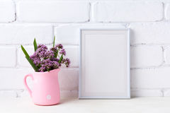 White frame mockup with purple flowers in pink rustic pitcher royalty free stock photography