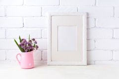 White frame mockup with purple flowers in pink rustic pitcher Stock Photos