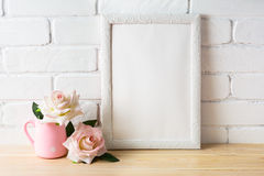 White frame mockup with two pale pink roses. White frame mockup with white and golden vases. Empty white frame mockup for design presentation. Portrait or poster stock photos