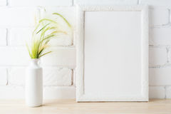 White frame mockup with wild grass ears near painted brick wall Stock Photo