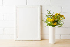White frame mockup with yellow flowers near painted brick walls Stock Photos