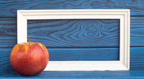 White frame and a red apple on a background of blue boards Royalty Free Stock Photos