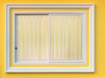 White frame window in yellow wall with curtain. Close-up background A window of white concrete framing in a yellow wall with a beautiful soft brown curtain ine Royalty Free Stock Images