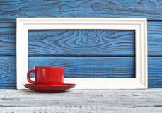 White frameand red coffee cup on a background of blue boards Stock Photo