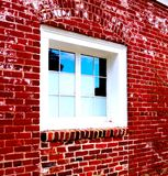 White Framed Window With Multiframed Squares Offset Vivid Red Bricks of Building stock image