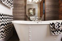 White free standing vintage style bath tub with chevron pattern Royalty Free Stock Image