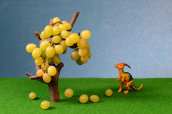 White fresh grapes and dinosaur figure Stock Photography