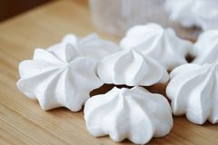 White fresh tasty meringues on wooden table stock photography