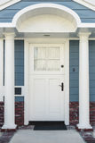 White front door of classical blue and brick home Stock Images