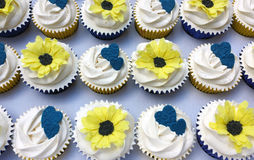 White frosted cupcakes with sunflowers and blue hearts. White frosted cupcakes with royal blue and yellow decorations. Topped with yellow sunflowers or also stock photography