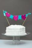 White frosting vanilla birthday cake with celebration banner. Gr. Ay background. Celebration concept Stock Images