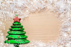White frosty branches, covered with snow, green glass toy Christmas tree and copy space on natural wooden background. stock photography