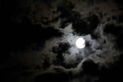 White full moon and eerie white clouds against a b Stock Images