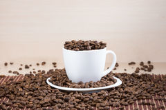 White full of roasted coffee beans cup standing on a white plate on tablemat. Royalty Free Stock Image