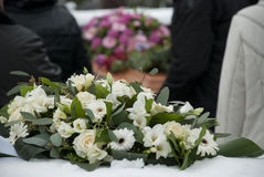 White Funeral flowers in the snow before a caket. White funeral flowers arrangement in the snow on a hedge at the cemetery before a casket stock image