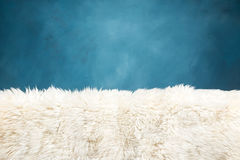 White fur carpet and blue painted wall Royalty Free Stock Image