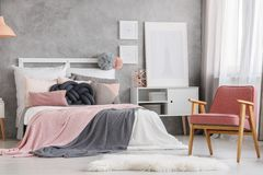 Unique pastel bedroom design. White fur and powder pink design chair in unique pastel bedroom with copper lamp on cupboard stock photography