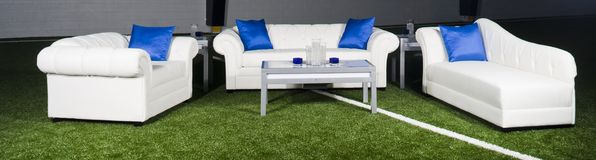 White furniture with blue accents. White couches with blue pillows set up in a large room stock images