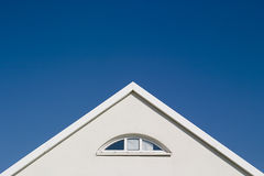 White gable - blue sky. White gable with window in front of a clear blue sky royalty free stock photo