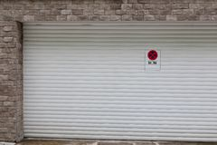 White garage door with no parking sign. Conceptual white garage door with no parking sign - tow car warning royalty free stock photos