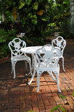 White garden chairs in a backyard patio Royalty Free Stock Photos