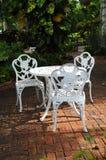 White garden chairs in a backyard patio. White ornamental garden chairs in a backyard patio with surrounding garden royalty free stock photos