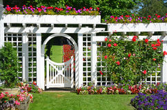 White garden gate with flowers Royalty Free Stock Image