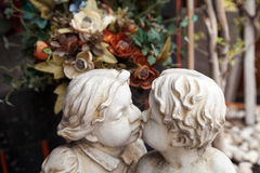 White garden sculpture of two kissing kids. Curly hair children angels kissing art statue of plaster Royalty Free Stock Photo