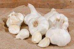 White garlic bulbs and cloves. On burlap Royalty Free Stock Photos