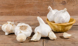 White garlic bulbs and cloves. On wooden background Royalty Free Stock Image